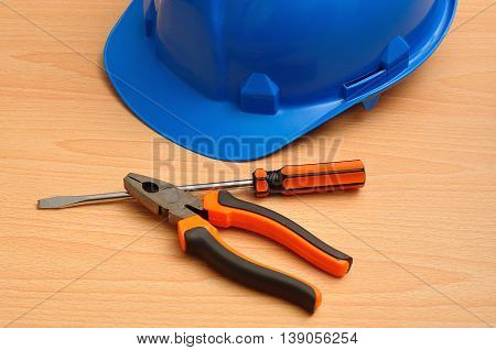A blue hard hat displayed with a screw driver and pliers
