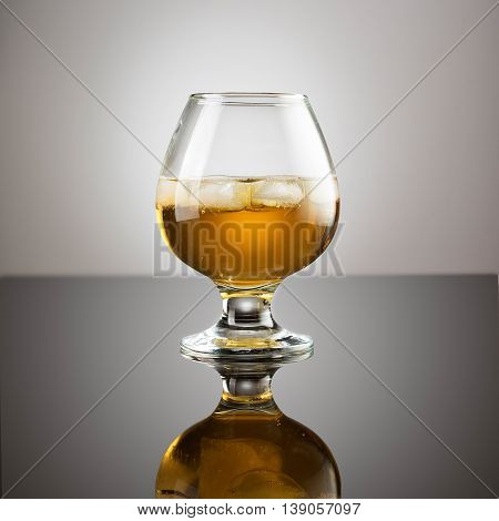 Drink in a glass on glossy surface with drops isolated