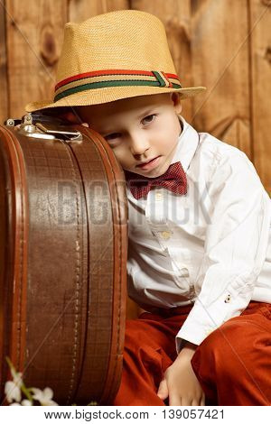 Cute little boy in elegant clothes sitting with his old suitcase over wooden background. Kid's fashion. Childhood.