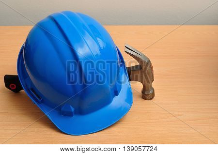 A blue hard hat displayed with a hammer