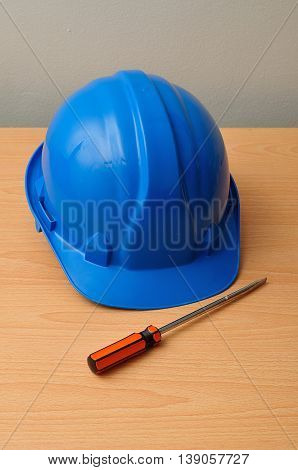 A blue hard hat displayed with a screw driver