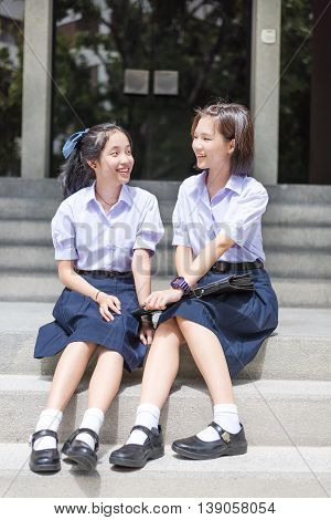 Cute Asian Thai high schoolgirls student couple in school uniform sit on the stairway chatting with a happy smiling and laughing face together on a building stairs