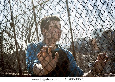 A Man outside close to a fence without feeling