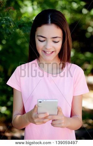 Adorable preteen girl with mobile with plants of background