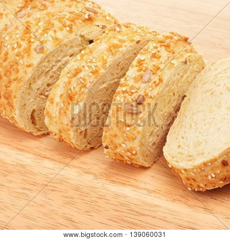 sliced corn bread with sesame and sunflower seeds on cutting board