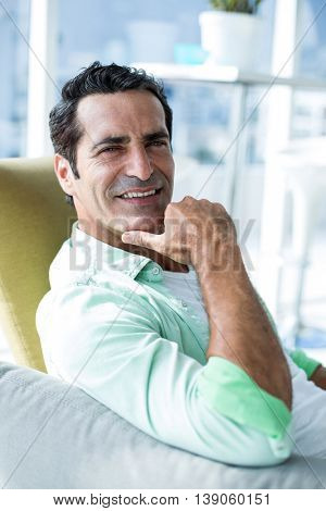 Portrait of man with hand on chin while resting at home