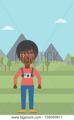 An african-american woman with a digital camera on her chest. Tourist with a digital camera standing on the background of mountains. Vector flat design illustration. Vertical layout.