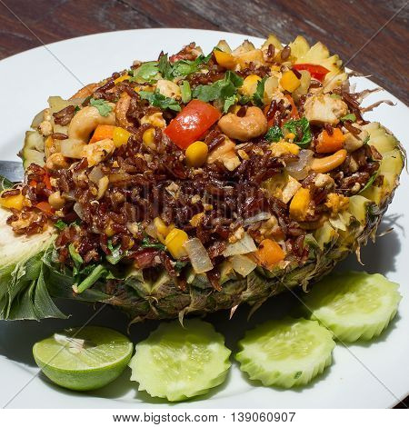 Cooked brown rice with vegetables and tofu in a pineapple close up