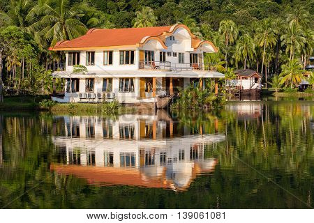 Exotic place coconut palm trees and lake water on tropical island Koh Chang Thailand