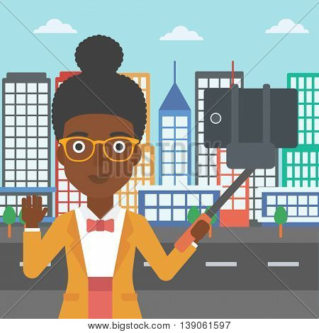 An african-american woman making selfie with a selfie-stick. An african-american woman taking photo with cellphone and waving on a city background. Vector flat design illustration. Square layout.