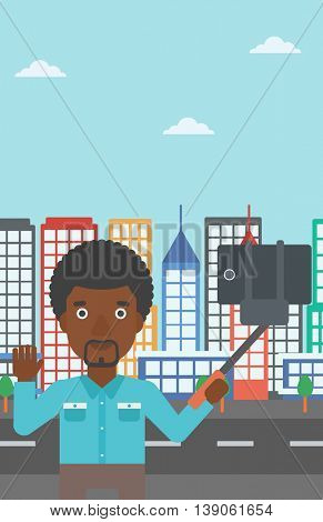 An african-american man making selfie with a selfie-stick. Man taking photo with cellphone and waving on a city background. Vector flat design illustration. Vertical layout.