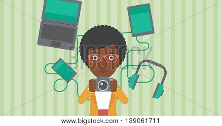 An african-american woman taking photo with digital camera. Woman surrounded with her electronic gadgets. Woman using many electronic gadgets. Vector flat design illustration. Horizontal layout.