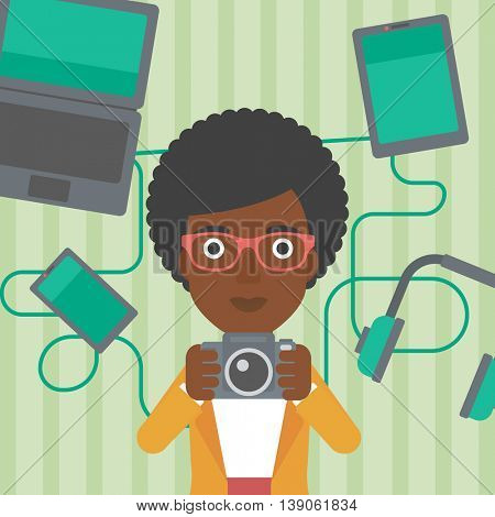 An african-american woman taking photo with digital camera. Woman surrounded with her electronic gadgets. Woman using many electronic gadgets. Vector flat design illustration. Square layout.