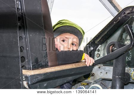 Little boy in the cockpit of an old propeller aircraft