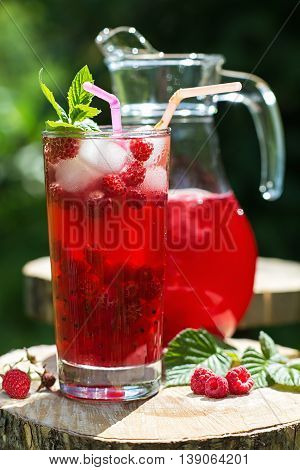Glass and jug of berry juice with raspberry and redcurrant with mint and ice in a summer garden