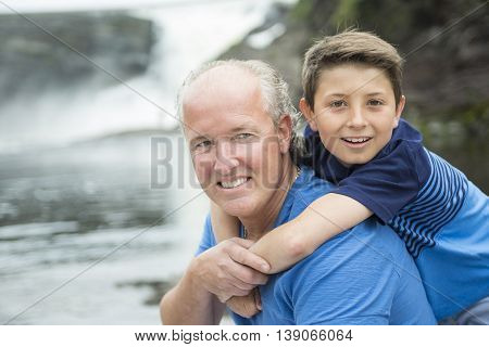 A Father and son outside in front of a waterfsll