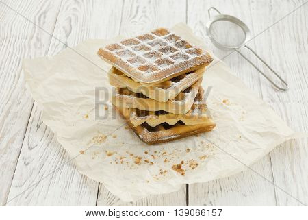 Homemade baking. Viennese waffles with powdered sugar on wrapping paper. Copy space composition