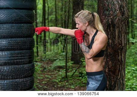 Woman boxer doing cross kick working out outdoors.