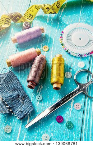 Set for sewing and needlework on a wooden board in Shabby Chic style - thread, seam ripper, scissors, buttons, pins