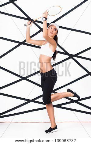 Young slim woman in trendy sportswear playing badminton