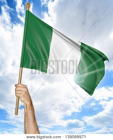 Person's hand holding the Nigerian national flag and waving it in the sky, 3D rendering