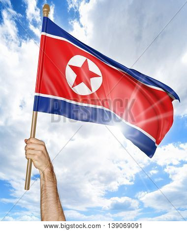 Person's hand holding the North Korean national flag and waving it in the sky, 3D rendering