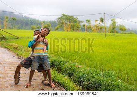 Mamasa, Indonesia - August 17, 2014: Two Unidentified Funny Children Playing, Smiling And Looking At