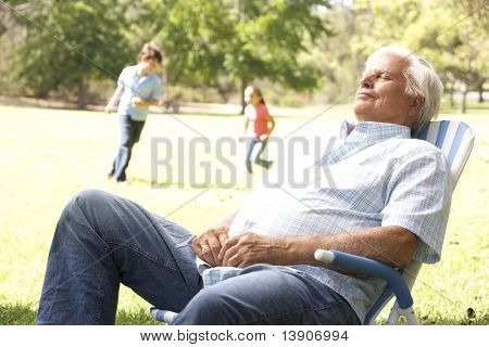 Senior Man Relaxing In Park With Grandchildren In Background
