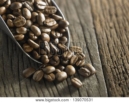 shovel of roasted coffee bean on the wooden background