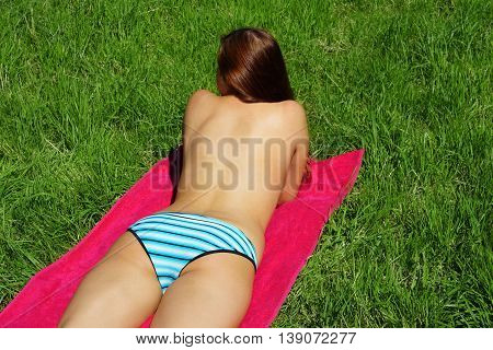 young woman wearing bikini bottoms lying on towel sunbathing