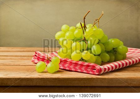 Grapes on checked tablecloth on wooden table over grunge background