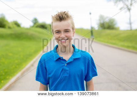 A Young happy smiling male boy teenager blond child outside in summer sunshine wearing a blue sweatshirt