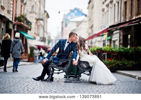 Wedding Couple In Love Siting On Bench At Street Of City