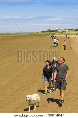 WEST KIRBY, ENGLAND, JULY 4. The Beach on July 4, 2016, at West Kirby, England. A steady procession of beach walkers stream back and forth between West Kirby and Hoylake England.