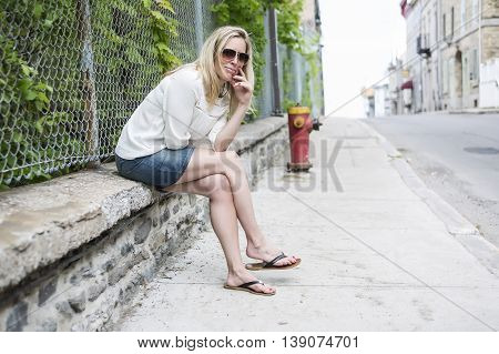 Woman Outdoors with sunglasses sit on a fence