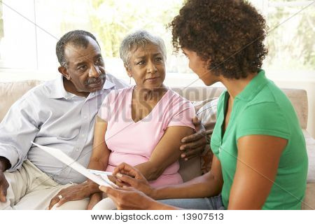 Senior Couple Talking To Financial Advisor At Home