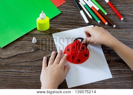 Child Glues Paper Details On A Postcard. The Child Makes A Postcard With Ladybird. Glue, Paper, Scis