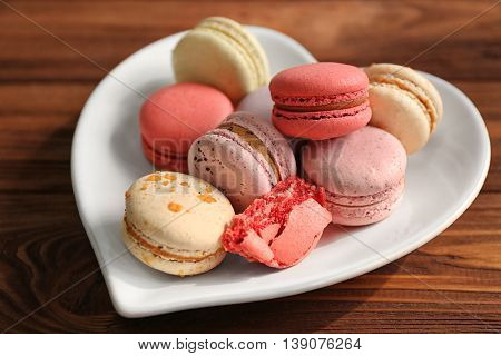 Tasty macaroons in heart shape plate on wooden background