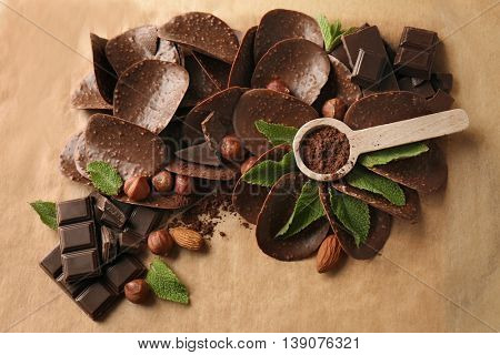 Composition of chocolate chips and spoon with cocoa powder on parchment background
