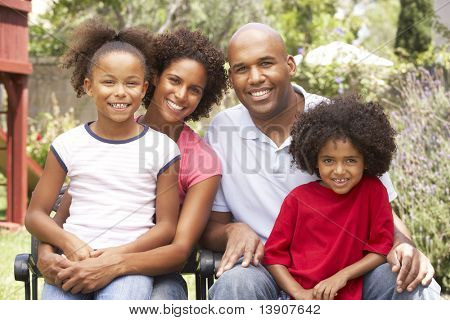 Young Family Relaxing In Garden Together