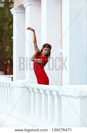 Beautiful girl posing like ballerina near the old mansion with columns