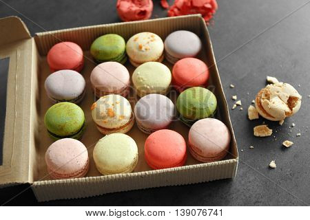 Different colorful macaroons in box on gray background