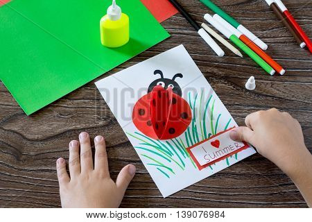 Child Glues Paper Details That I Love Summer. The Child Makes A Postcard With Ladybird. Glue, Paper,