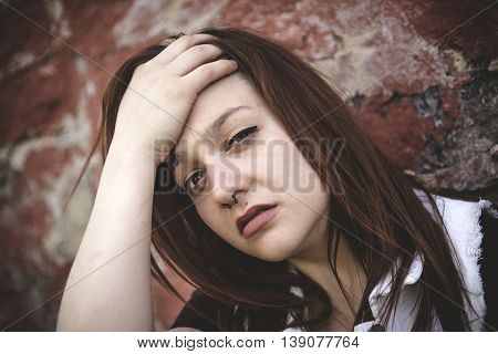 A Sad girl with motional face brick background