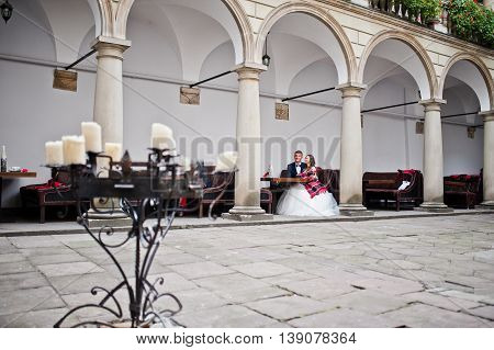 Newlyweds Sitting At The Table Near Columns, Bride With Blankets