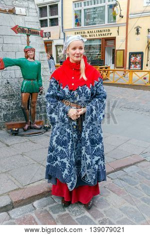 Tallinn Estonia - October 18 2015: The girl in the national costume about a famous local restaurant Olde Hansa in Tallinn.