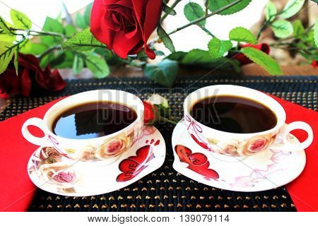 Two romantic cups of coffee with white and red flowers on the dark blue bamboo napkin. Coffee service with red love hearts.