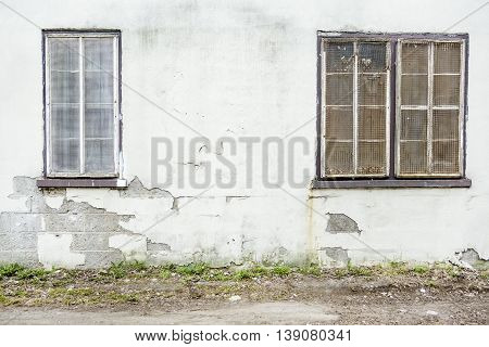 An abandoned grunge cracked brick stucco wall with a window grilles