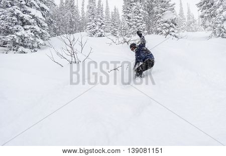 A snowboarder descends down the mountain in the snowy woods looking into the camera and waving