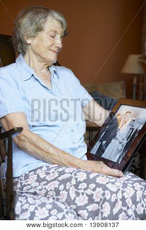 Senior Woman zu Hause Blick auf alte Hochzeitsfoto